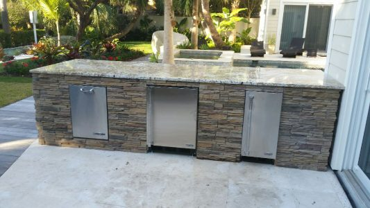 Outdoor Kitchen in Casey Key with Ice Maker, Fridge and Trash Bin