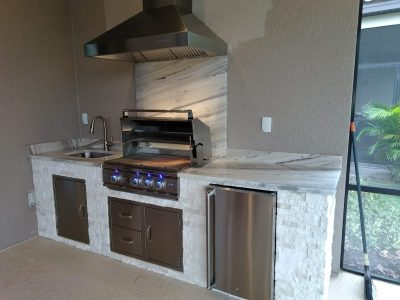 outdoor kitchen with hood vent and Summerset grill