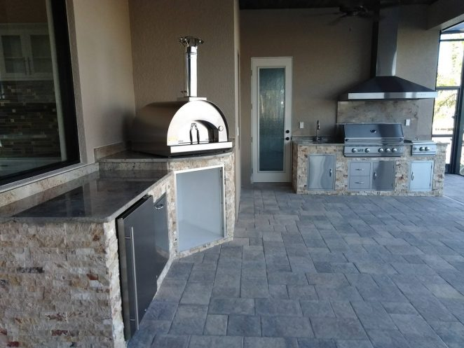 custom outdoor kitchen layout accommodates the customer's desired appliances - including a pizza oven