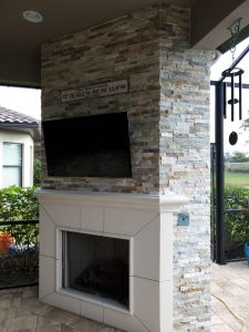 outdoor fireplace with a flatscreen TV above the mantel