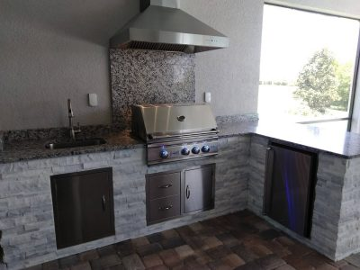 outdoor kitchen with grill, sink and fridge