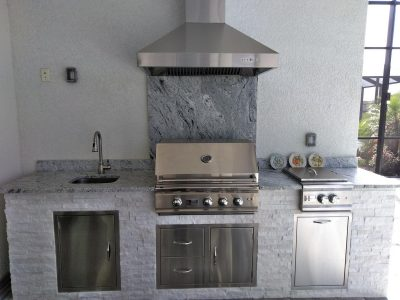 gray outdoor kitchen with grill, hood vent and power burner