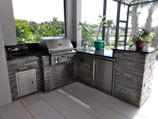 beautiful outdoor kitchen with gray stone and black granite