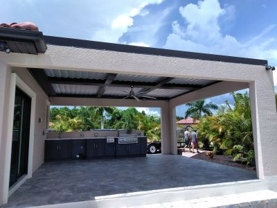 outdoor kitchen under a large covered area with a louvered pergola
