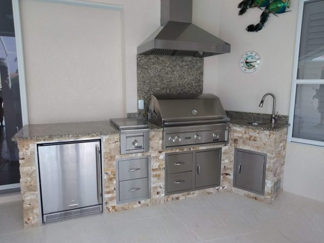 outdoor kitchen with grill, hood vent, fridge, burner and sink
