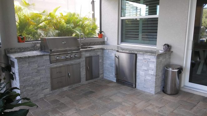reverse l-shape outdoor kitchen with gray stone and granite